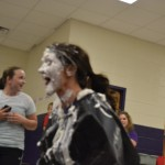 "Ms. Johnston enjoys her whip cream facial at ""Pie the Teacher,"" while Ms. Simpson cleans up after receiving her pie."