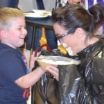 Mrs. Garcia receives her pie. Her class raised $200 in the PTO Write A Check Fundraiser